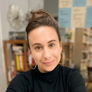 Head and shoulders shot of Liza Minno. She is facing the camera, head tilted left, wearing a black top, silver hoop earrings, and with her light brown hair done up in a bun. In the background is a room with several bookcases.