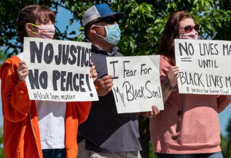 Two white woman and a black man holding signs regarding racial justice