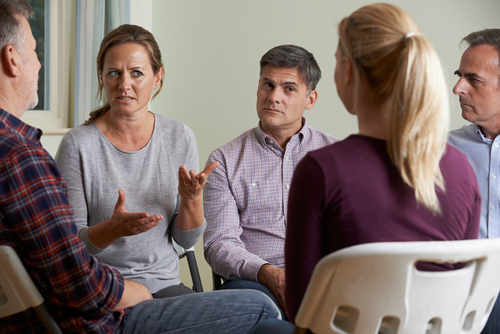 Group of six white people sitting in a circle engaged in earnest discussion