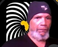 Head shot of Robin Benton. He is wearing a dark blue shirt and ski cap, facing the camera with his shoulders turned slightly to the right. He is sporting a mustache and goatee with gray hair. In the background is a black and white graphic design with a yellow silhouette of the African continent in the center.