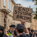 Close up view from the rear of a crowd of young, mostly white, people in a public square. One man wearing a baseball cap holds up a sign saying End Systemic Racism. A woman to his left looks back facing the camera.