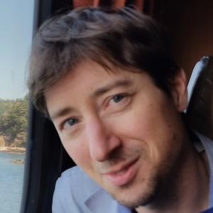 headshot of Jordan Margolis, wearing allight blue dress shirt, siting inside a car next to a window with head tilted.