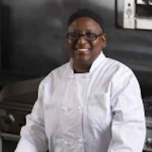 Upper body shot of Pearl Thompson. She is wearing a white chef's outfit. In the background is a commercial kitchen with stove and microwave. She is wearing glasses, facing the camera directly and smiling.