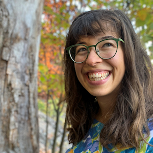 Head and shoulders shot of Suzy Jivitovski. She has brown hair falling below her shoulders and is wearing oversized glasses and a blue print upper garment while standing in a wooded setting. Her shoulders and body face left and her head is turned toward the camera smiling.