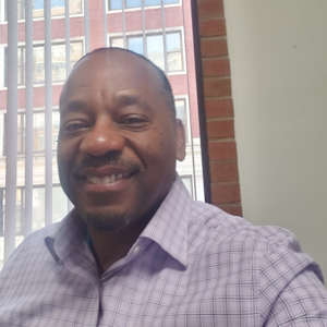Head and shoulders shot of Alvin Gray. He is wearing a lavender checkered dress shirt and standing with an interior sunlit window in the background. He is facing the camera at a slight angle and smiling.